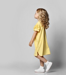 Little blonde curly girl in yellow dress and sneakers walking and looking up over grey wall background, side view. Stylish casual fashion for children