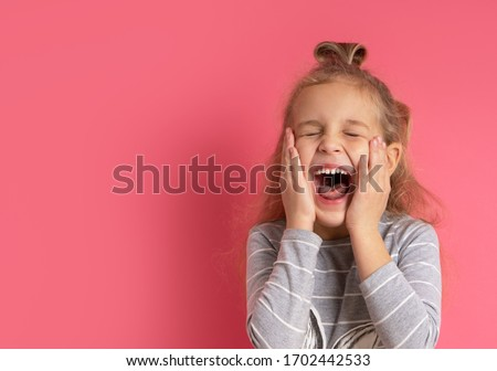 Little blonde female with bun hairstyle, dressed in gray striped blouse. She laughing out loudly, touching cheeks, posing against pink background. Childhood, fashion, advertising. Close up, copy space Stock photo ©