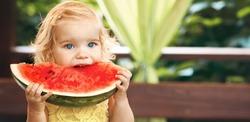 Little blonde girl eating a juicy watermelon in the garden. Children eat fruit on the street. Healthy food for children. Toddler gardening.Long banner format.