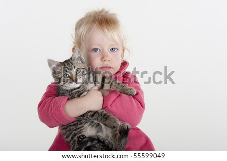 little blonde girl hugging cute pet gray tabby kitten