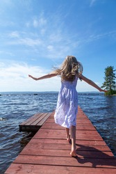 Little blonde girl in a white dress running on a wooden pier, surrounded by water, and enjoying the beautiful view of the lake in summer, back view, vertical