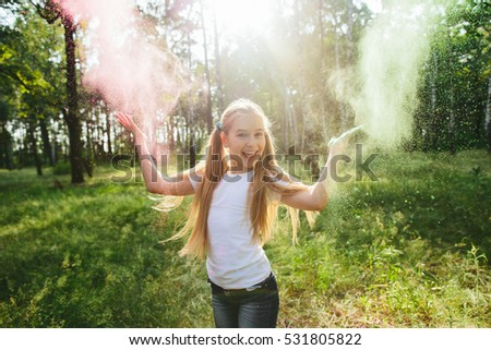 Little blonde girl in shorts and a white T-shirt in the park playing with dry paint and smiles #531805822