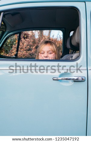 Little blonde girl in the car window #1235047192