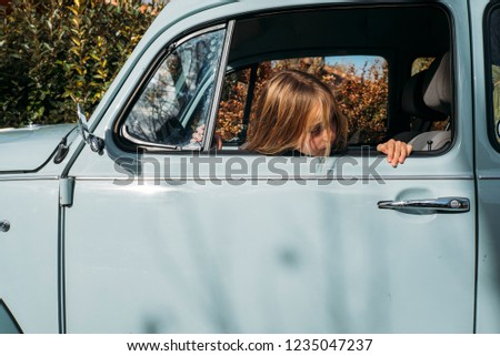 Little blonde girl in the car window #1235047237