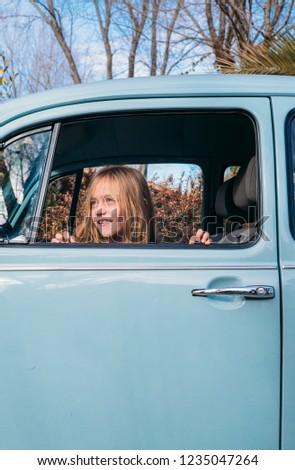 Little blonde girl in the car window #1235047264