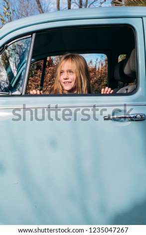 Little blonde girl in the car window #1235047267
