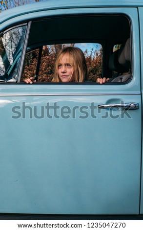 Little blonde girl in the car window #1235047270