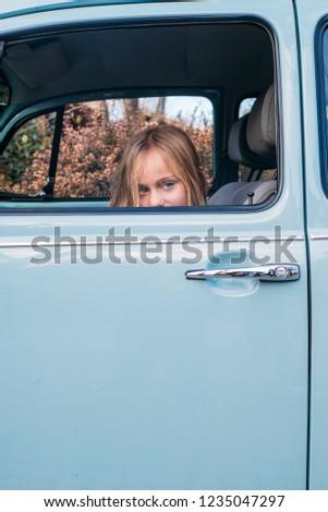 Little blonde girl in the car window #1235047297