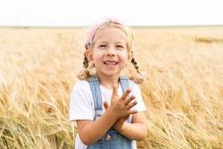Little blonde girl in the field of rye, grain harvest.