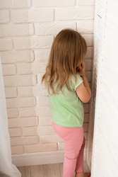 little blonde girl is punished and stands alone in a corner and cries. The child misbehaved and was put in a corner to calm her down. Education and punishment of children by parents.