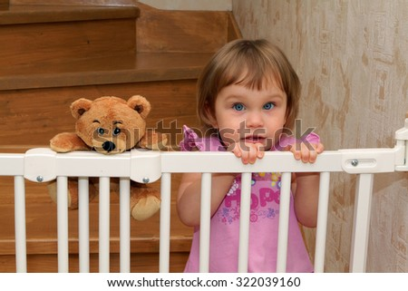 Little blonde girl on the stairs with a gate with a teddy bear friend