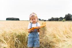 Little blonde girl plays plane in the field of rye, grain harvest.