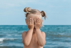 Little blonde girl stands on a background of the sea and covers her face with her hands