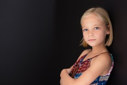 Little blonde girl with a serious expression on her face while standing against a black wall.