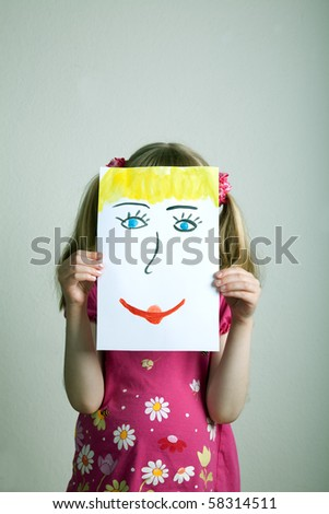 Little blonde girls holding happy face mask