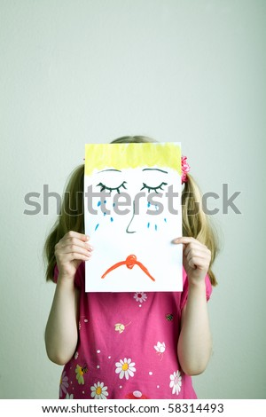 Little blonde girls holding sad face mask