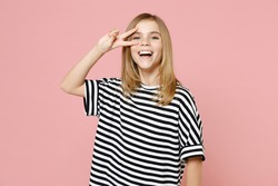 Little blonde smiling kid girl 12-13 years old wearing striped oversized t-shirt cover eye with victory v-sign gesture isolated on pastel pink background children studio. Childhood lifestyle concept