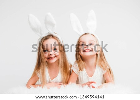 Little blonde twins in white dresses with rabbit ears. Studio photo on gray background. Kids celebrate Easter.