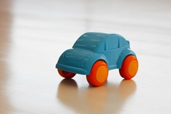 little blue baby car with orange wheels