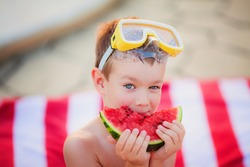 Little blue-eyed blond boy wearing yellow Diving Goggles eating watermelon sitting on the striped red and white beach towel in the summer