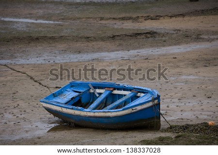 Little boat at low tide. Blue old boat stranded on beach at low tide. Asturias, North Spain.