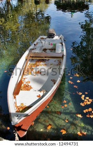 Little boat Canal and boat, covered with autumn leaves, a bright sunny noon