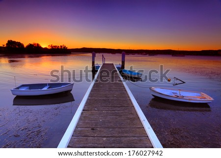 Little boats moored to a jetty at sunset.This is a quiet cove on the Brisbane Waters, Central Coast Australia