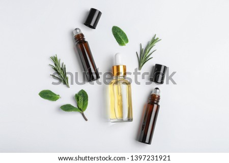 Little bottles of essential oils with different herbs on white background, top view #1397231921