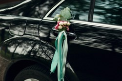 Little bouquet of roses and green ribbons hangs on the door's handle