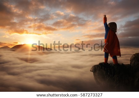 Little boy acting like a superhero on top of the mountain at sunset with copy space #587273327