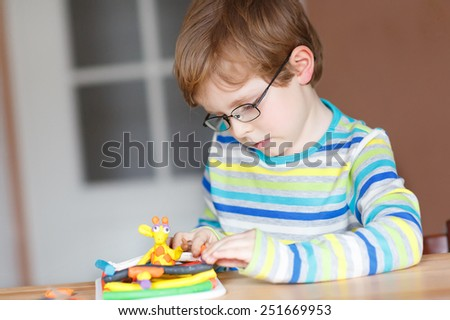 Little boy, adorable creative kid boy with glasses playing with dough, colorful modeling compound, sitting at table at home or in school room. Creative leisure with kids.