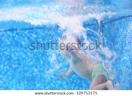 Little boy after diving into a swimming pool, hand and water bubbles in focus