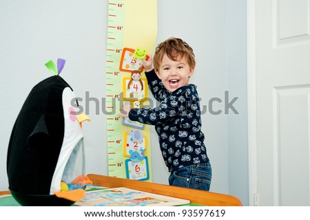 Little boy age 3 laughing and playing in his room