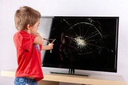 Little boy aiming to a cracked TV screen with a slingshot.