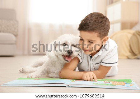 Little boy and bichon frise dog reading book at home #1079689514