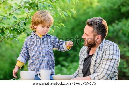 Little boy and dad eat. Organic nutrition. Healthy nutrition concept. Nutrition habits. Family enjoy homemade meal. Personal example. Nutrition kids and adults. Father teach son eat natural food.
