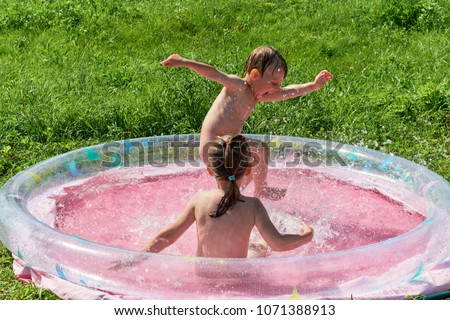 Little boy and girl are swimming in the inflatable outdoor pool. The boy stomps his foot and splashes fly to the sides. Baby waving his hands. Girl splashing around and looking at the boy.