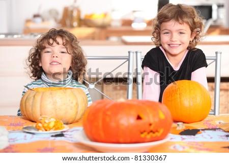 little boy and girl dressed in pajamas posing behind pumpkins