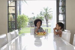 Little boy and girl eating fruit salad at dining table