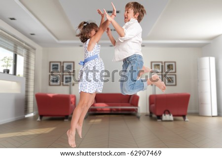 Little boy and girl happily jumping on a home interior