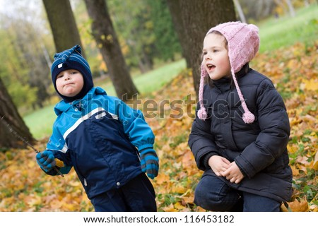 Little boy and girl having fun in an autumn park