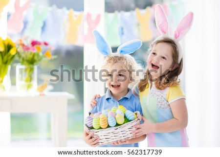 Little boy and girl in bunny ears holding a basket with colorful Easter eggs. Kids celebrating Easter. Children having fun on Easter egg hunt. Home decoration - pastel color bunny banner and flowers #562317739