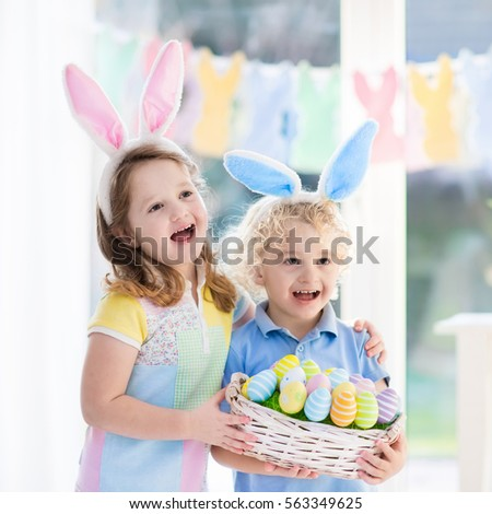 Little boy and girl in bunny ears holding a basket with colorful Easter eggs. Kids celebrating Easter. Children having fun on Easter egg hunt. Home decoration - pastel color bunny banner and flowers #563349625