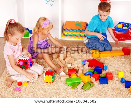 Little boy and girl in kindergarten stacking block.
