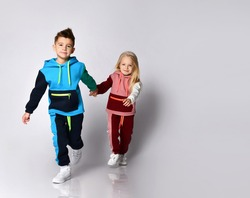 Little boy and girl in sportsuits walking forward hand in hand. Young athletes, being stylish, friendship, loving brother and sister. Full length portrait isolated on light grey, copy space