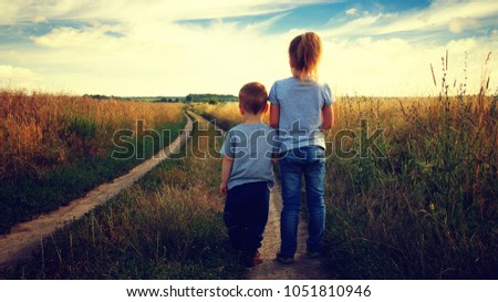 little boy and girl in the field looking the landscape