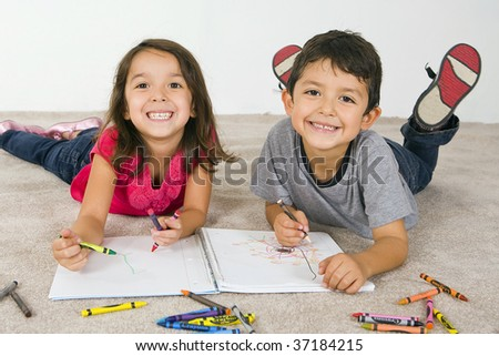 Little boy and girl laying on the carpet coloring