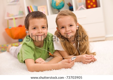 Little boy and girl listening to music together sharing earphones, laying on the floor at home