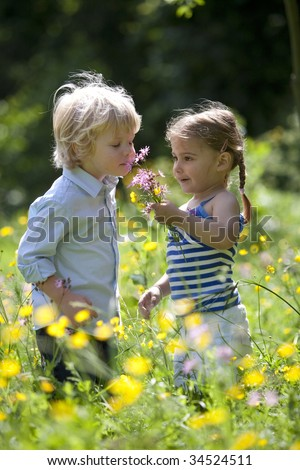 Little boy and girl picking and smelling  flowers in the parc