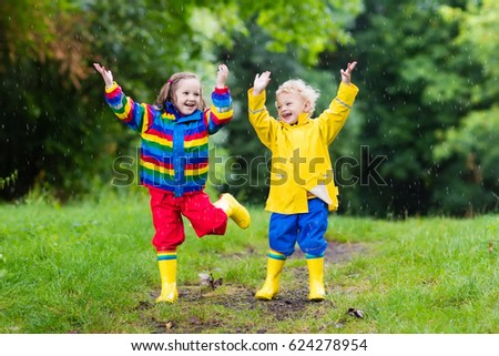 Little boy and girl play in rainy summer park. Children with colorful rainbow jacket and waterproof boots jump in puddle and mud in the rain. Kids walk in autumn shower. Outdoor fun by any weather.